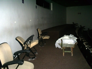 Na única sala que havia sido entregue, cadeiras quebradas e sujeira predominam entre o breu.